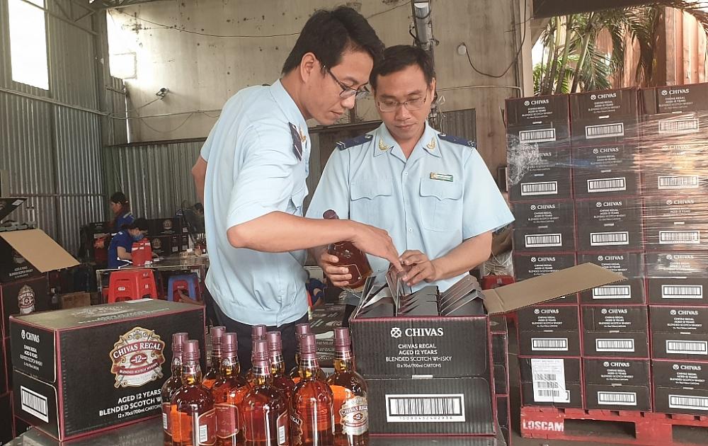 Công chức Hải quan Bình Dương kiểm tra rượu NK Ảnh: Đăng Nguyên