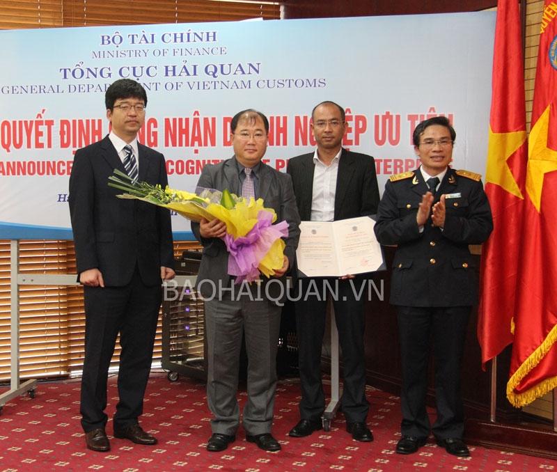 Phó Tổng cục trưởng Tổng cục Hải quan Nguyễn Dương Thái trao quyết định công nhận DN ưu tiên và tặng hoa chúc mừng đại diện SEVT ngày 3-3-2014. Ảnh: T.Bình.