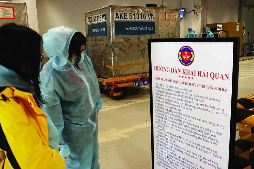 Công chức Hải quan sân bay Vân Đồn trong bộ đồ bảo hộ chống Covid-19 đang làm thủ tục cho hành khách nhập cảnh về nước tránh dịch.