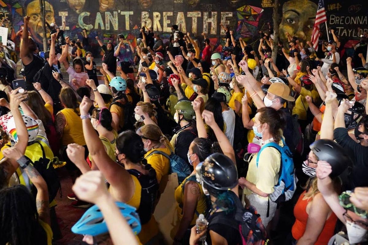 """Những người biểu tình diễu hành qua một bức tranh trên tường ghi lại những lời cuối cùng của George Floyd - """"I can't breath"""" (Tôi không thở được). Ảnh: Getty Images"""